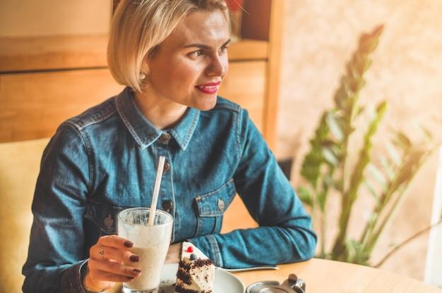 Schönes mädchen in einem café, das einen kalten cocktail genießt. hipster-mädchen, das sommercocktail hält. erfrischungsgetränk an einem sonnigen tag