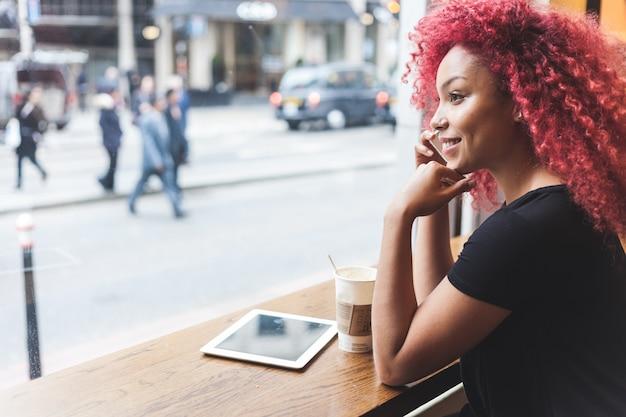 Schönes mädchen in einem café sprechend am intelligenten telefon
