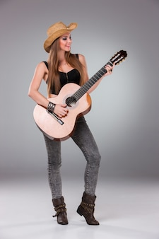 Schönes mädchen in einem cowboyhut und einer akustischen gitarre.