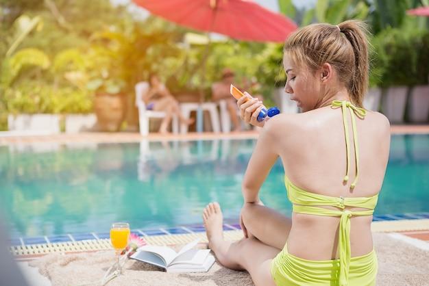 Schönes mädchen in einem grünen badeanzug, der auf dem pool an ihrer freizeit ein sonnenbad nehmend sitzt