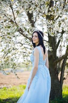 Schönes mädchen in einem hellen sommerblauen langen kleid, das in ihrem haar gegen einen blühenden baum geschmückt ist. zartes porträt einer jungen frau in weißer blüte
