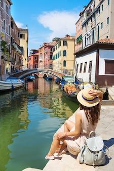 Schönes mädchen in einem hut sitzt nahe einem kanal in venedig, italien