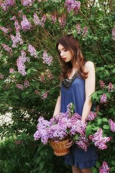 Schönes mädchen in einem kleid, das in bush von fliedern aufwirft