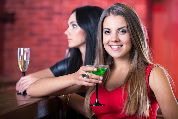 Schönes mädchen in einem kleid trinkt ein cocktail und lächelt