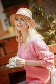 Schönes mädchen in einem rosa kleid, das in einem café mit einer tablette und einer tasse cappuccino sitzt. junge glückliche frau, die tablet-computer in einem café verwendet.