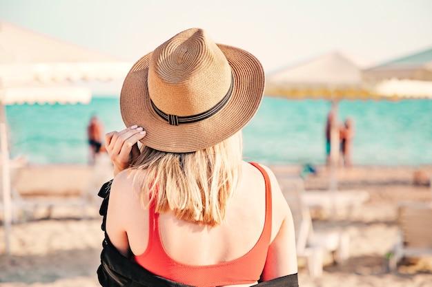 Schönes mädchen in einem roten bikini und strohhut am strand