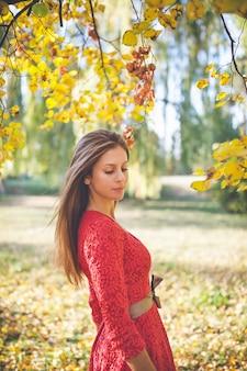 Schönes mädchen in einem roten kleid in einem herbstpark