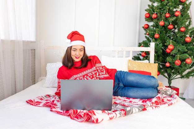 Schönes mädchen in einem roten pullover, der an einem laptop zu hause auf bett nahe weihnachtsbaum arbeitet