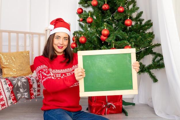 Schönes mädchen in einem roten pullover nahe dem weihnachtsbaum hält eine tafel mit platz für text