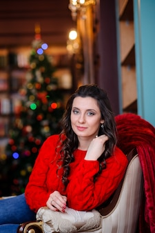 Schönes mädchen in einem roten pullover nahe dem weihnachtsbaum.