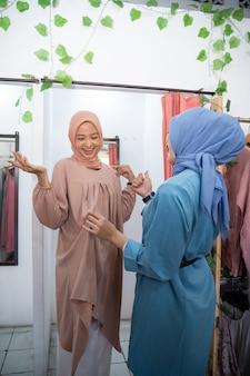 Schönes mädchen in einem schleier, das in einer umkleidekabine vor dem spiegel kleidung anprobiert, damit ihre f...