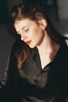 Schönes mädchen in einem studio. stilvolle frau in einem schwarzen kleid.