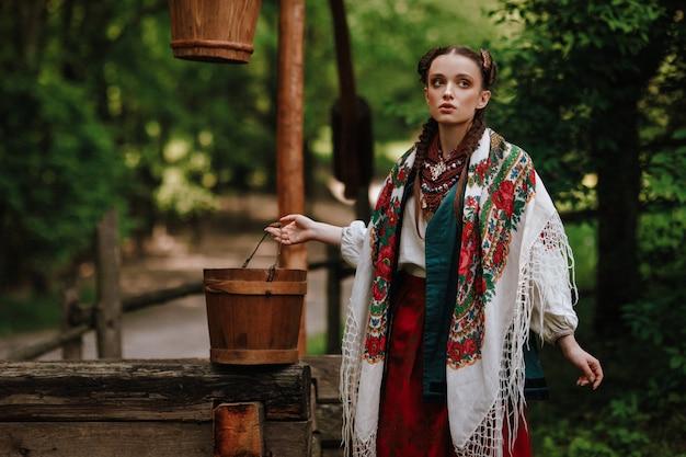 Schönes mädchen in einem traditionellen ethnischen kleid wirft am brunnen auf