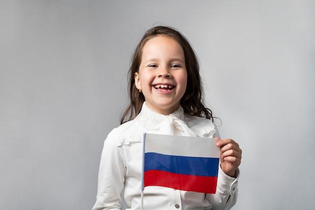 Schönes mädchen in einem weißen hemd, das die flagge der russischen föderation hält.