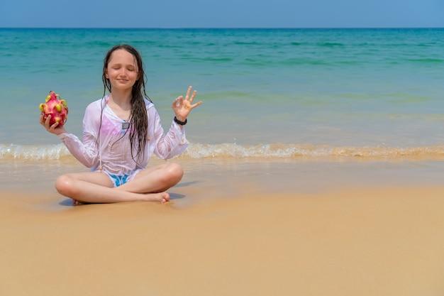 Schönes mädchen in einem weißen hemd meditiert an einem sonnigen tag vor dem hintergrund des meeres. glückliches kind auf dem ozean mit kopienraum. konzept des sonnigen und glücklichen sommers.