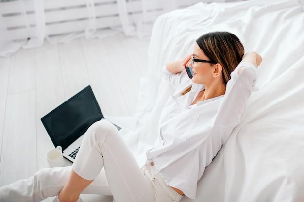 Schönes mädchen in einem weißen hemd ungefähr 25 jahre alt, das am telefon spricht, das auf dem boden nahe dem weißen bett zu hause sitzt
