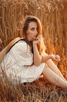 Schönes mädchen in einem weißen kleid. frau in einem herbstfeld. dame in einem strohhut.