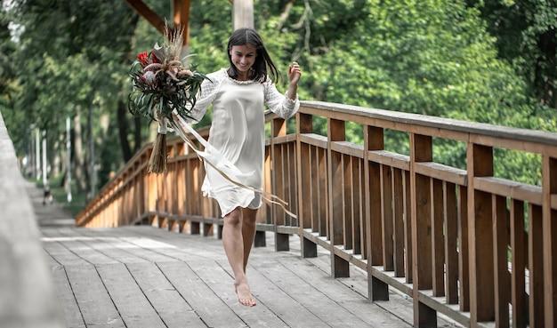 Schönes mädchen in einem weißen kleid mit einem blumenstrauß exotischer blumen auf einer holzbrücke.