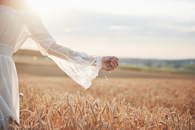Schönes mädchen in einem weizenfeld in einem weißen kleid, ein perfektes bild im stil lebensstil.