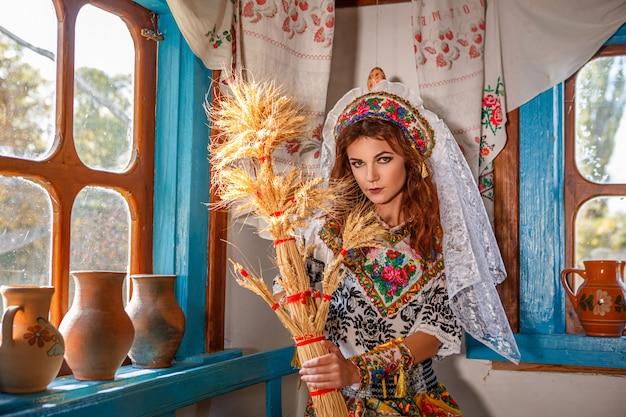 Schönes mädchen in einer hütte im nationalen slawischen kostüm.