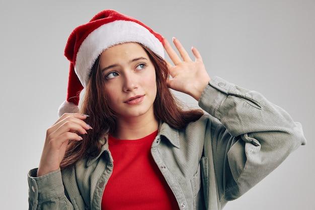 Schönes mädchen in einer jeansjacke und einem roten t-shirt mit einer weihnachtsmütze auf ihrem kopf