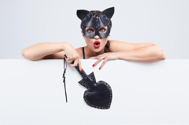 Schönes mädchen in einer katzenmaske. gibt den freien speicherplatz für den text an.