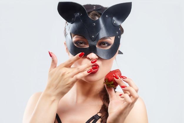 Schönes mädchen in einer katzenmaske. verführerisch mit erdbeeren posieren
