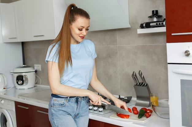 Schönes mädchen in einer küche mit gemüse