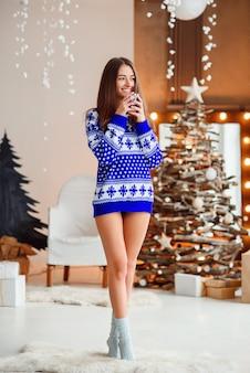 Schönes mädchen in einer warmen feiertagsstrickjacke mit einer tasse warmem tee mit zimt