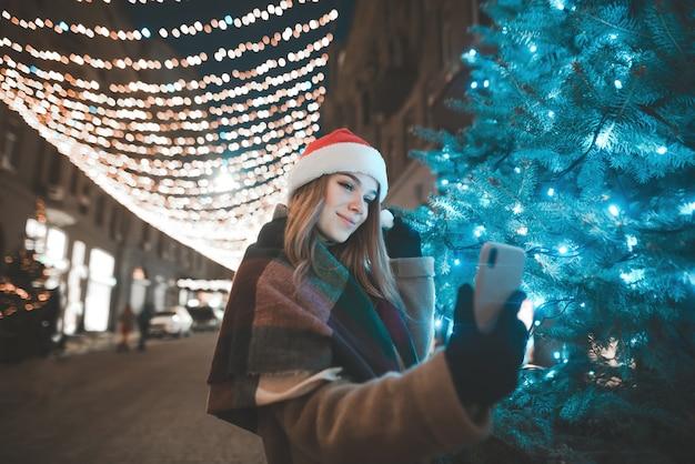 Schönes mädchen in einer weihnachtsmütze steht nachts auf einer straße in der nähe eines weihnachtsbaumes und macht ein selfie