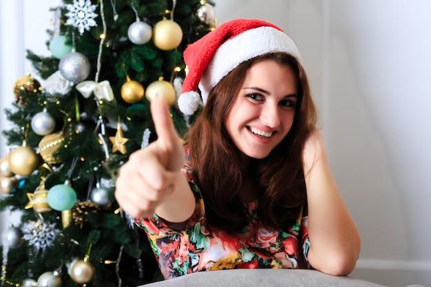 Schönes mädchen in einer weihnachtsmütze zeigt daumen hoch zeichen ok