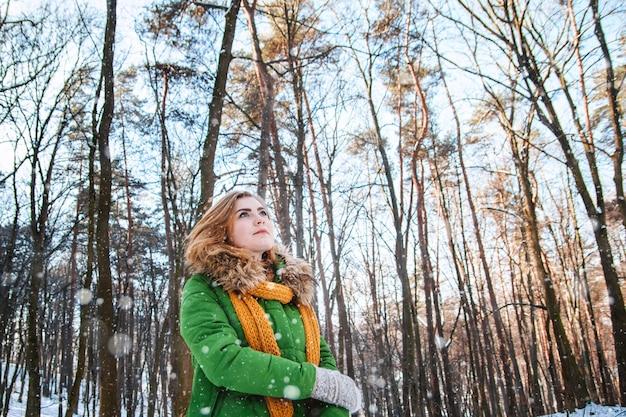 Schönes mädchen in einer winterjacke und in handschuhen auf einem waldhintergrund