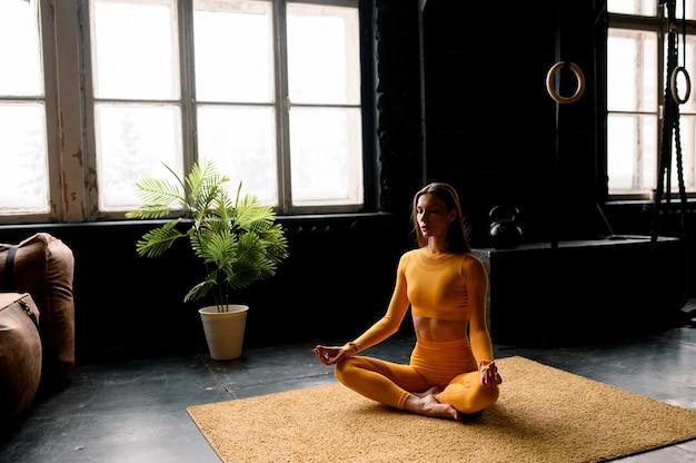 Schönes mädchen in gelber sportkleidung macht beim yoga richtig moderne sporthalle atmet