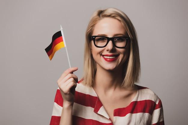 Schönes mädchen in gläsern hält deutsche flagge