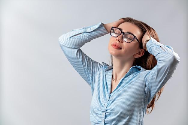 Schönes mädchen in gläsern und einem blauen hemd lokalisiert auf einer weißen wand