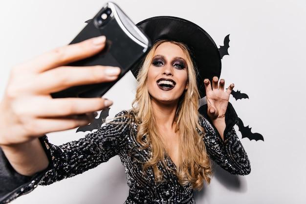 Schönes mädchen in hexenkleidung, das selfie am karneval macht. langhaarige blonde dame, die in halloween chillt.