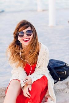Schönes mädchen in rotem kleid und weißer jacke sitzt auf einem pier, lächelt breit und hört musik auf kopfhörern auf einem smartphone