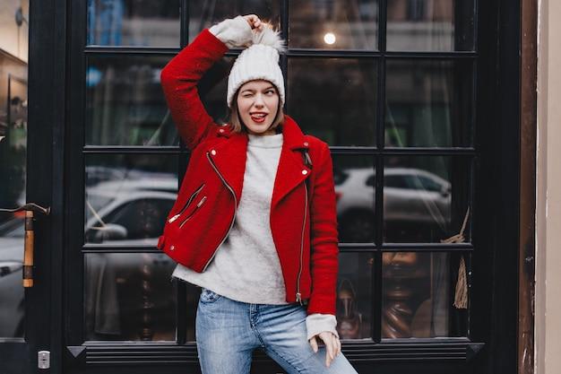 Schönes mädchen in rotem mantel und jeans hat spaß, zwinkert, zeigt ihre zunge und hält strickmütze pompon gegen fenster.