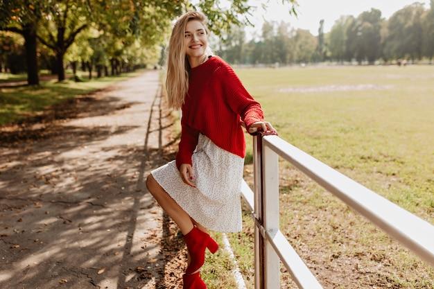 Schönes mädchen in roten schönen schuhen und weißem kleid amüsiert sich im park. schöne blonde frau, die spielerisch nahe gelben gefallenen blättern aufwirft.