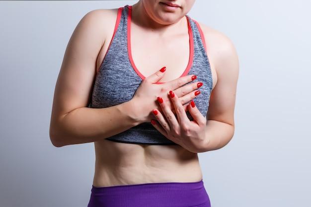 Schönes mädchen in sportkleidung berührt ihre brust und fühlt schmerzen auf grauem hintergrund