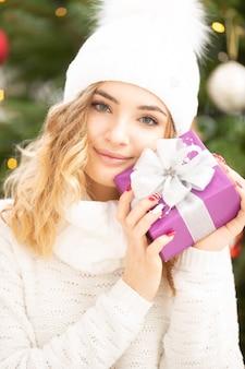 Schönes mädchen in weißem pullover und mütze hält ein ordentlich verpacktes weihnachtsgeschenk lächelnd.