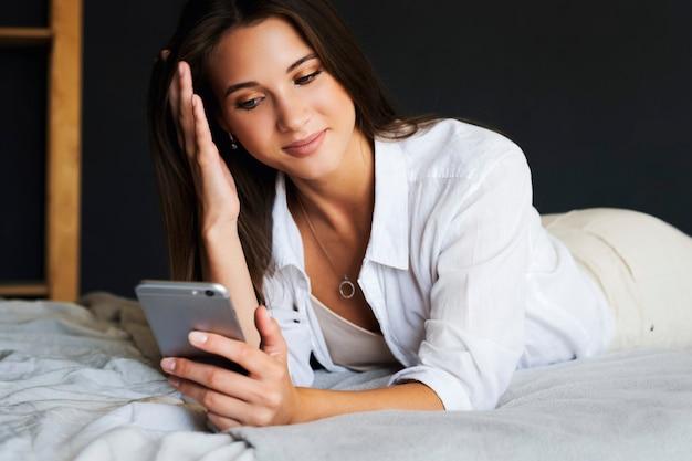 Schönes mädchen in weißen kleidern liegt bequem auf dem bett im schlafzimmer, nutzt smartphone, um mit freunden zu kommunizieren. unterhaltungsvideoinhalte tragbare verbundene geräte für hobbys, freizeit, zeitvertreib