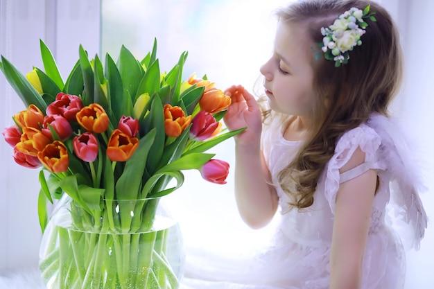 Schönes mädchen in weißen kleidern mit einem herrlichen strauß der ersten tulpen. internationaler frauentag. mädchen mit tulpen.