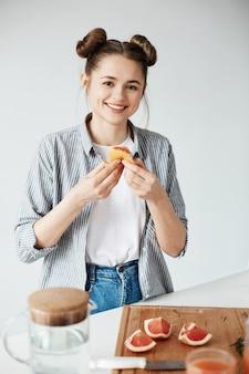 Schönes mädchen lächelnd, das grapefruitfrieden über weißer wand hält. gesunde fitnessernährung.
