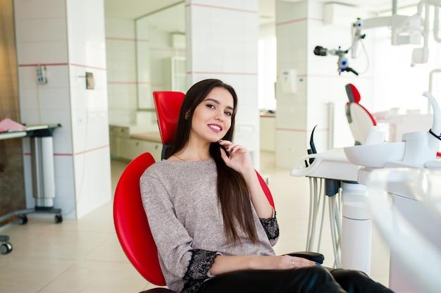 Schönes mädchen lächelt in den zahnarztstuhl.