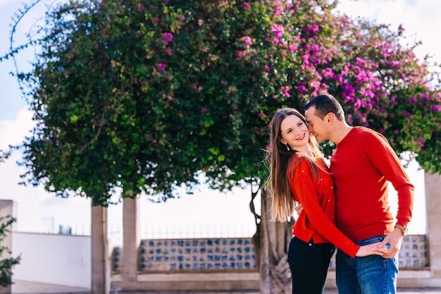 Schönes mädchen lächelt und kerl umarmt sie. verliebtes paar in roten pullovern. baum mit schönen blumen im hintergrund.