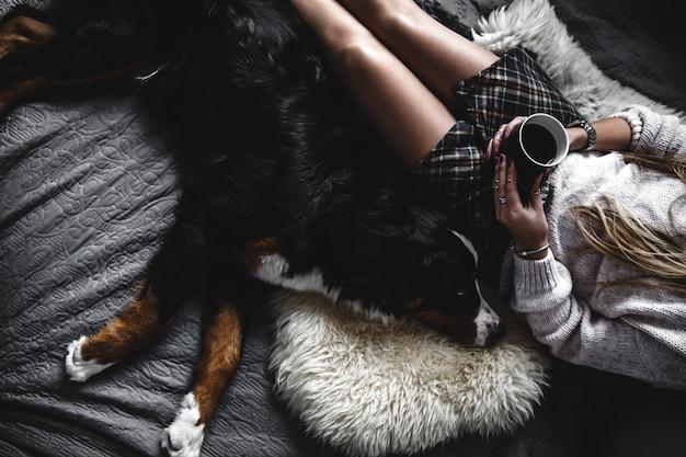 Schönes mädchen liegend und ihr süßer hund berner sennenhund auf bett, stilvoll, modisch, gemütlich