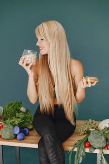 Schönes mädchen machen einen salat. sportliche blondine in einer küche. frau mit hafer.