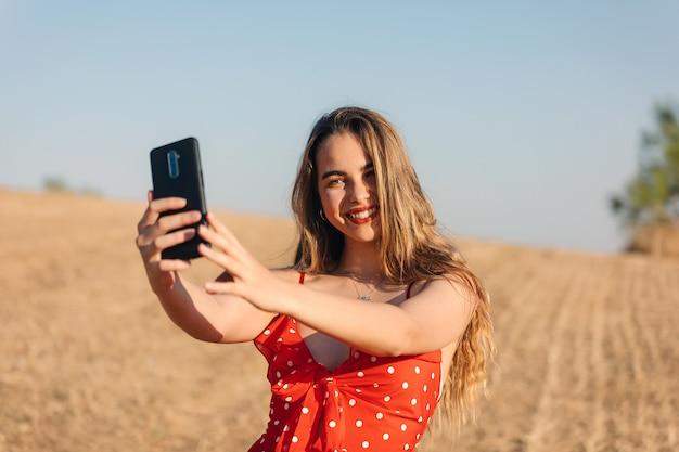 Schönes mädchen macht ein selfie im freien in einem sommersonnenuntergang