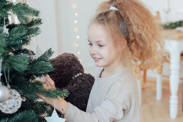 Schönes mädchen mit 8-jährigen nahe bei weihnachtsbaum